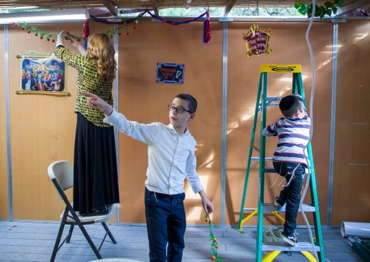 Uri Basser, 13, helps his family decide where to hang more holiday decorations inside the family sukkah. For the Orthodox community, Sukkot is the most joyous holiday of the year.