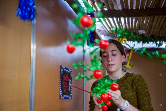 Devorah Basser, 16, ties up a plastic tomato vine that will hang from the sechach, or ceiling, of her family's sukkah in Lakewood. Ornaments should not hang low enough to brush against people's heads during Sukkot.