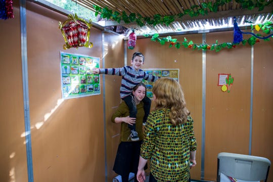 Devora Basser, 16, carries her brother Shimon, 6, over her shoulders as their mother, Nechama, 44, looks at the Sukkot decorations they just put on the walls of the family sukkah.
