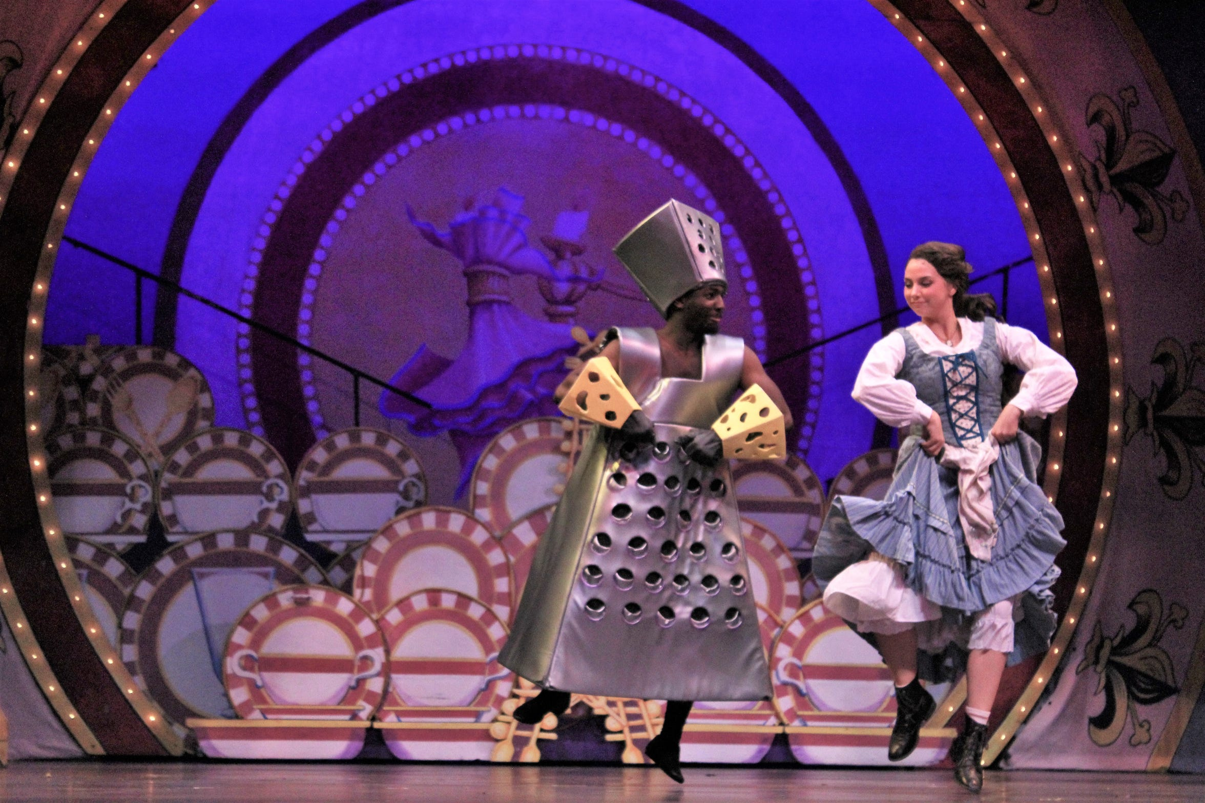 Belle (Lauren McDonald) shares a few nifty dance steps with a cheese grater (Jeremiah Taylor).