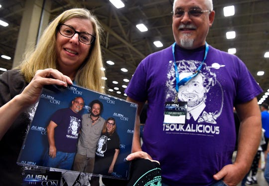 Karen and David Robertson of Austin hold the photograph they took with Ancient Aliens personality Giorgio Tsoukalos at AlienCon Dallas Oct. 5. David said they have been fans of the History channel show since it started and were celebrating their 25th wedding anniversary at the convention.