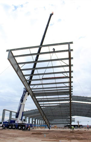 A crane Tuesday slowly lifts a 34,000-pound steel frame, one of 14 pieces that will form the roof structure of the new indoor event center at the Taylor County Expo Center. This was the final piece that would be fitted against No. 13 and bolted together. Oct. 15, 2019