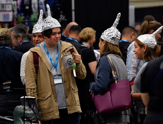 "Robert Zamora Jr. shops with his father Robert Sr., mother Sandra and sister Wendy in the Dallas AlienCon Marketplace Oct. 5. The family drove eight hours from Brownsville and made their foil hats earlier that morning, using the movie ""Signs"" for inspiration."