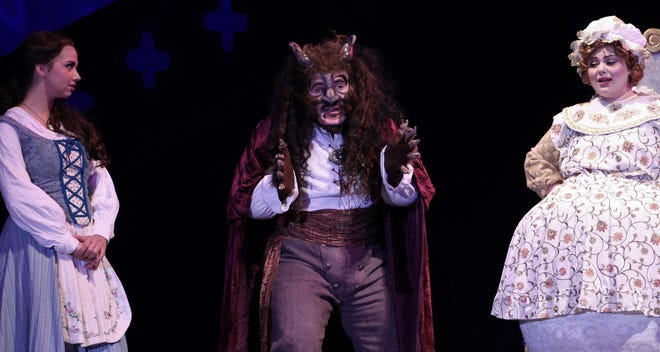 """The Beast (Richard Gomez) struggles with his tone and words while inviting Belle (Lauren McDonald) to join him for dinner as Mrs. Potts (Nora Vellis) encourages him in Abilene Christian University's production of """"Beauty and the Best,"""" performed as the 2019 homecoming musical."""