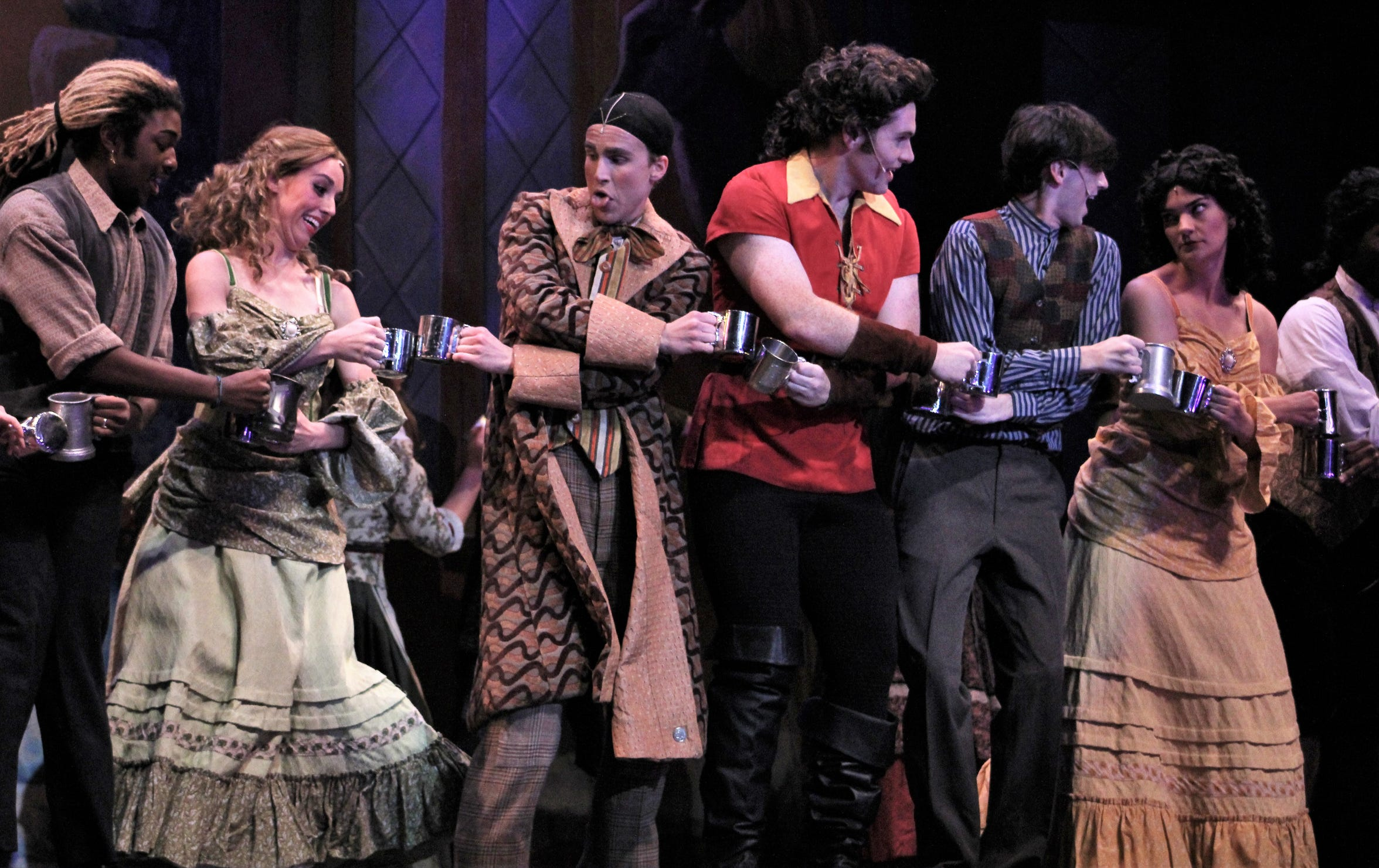 "Gaston (Griffin Jones, center) and his sidekick Lefou (Easton Orr) join others in a dance that includes the clanging of metal cups in Abilene Christian University's production of ""Beauty and the Beast."" ACU recently launch a dance track, which is allowing for more intricate sequences in stage shows."