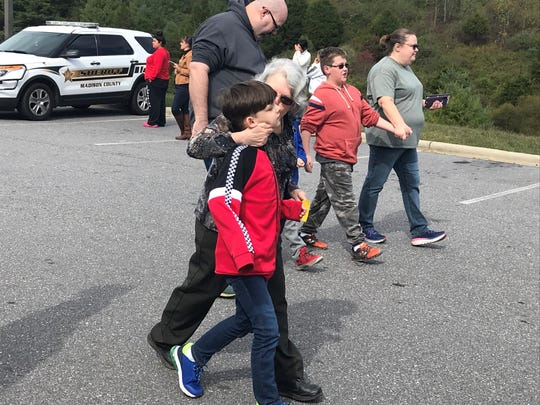 Relieved parents and family members leave the Madison County Sheriff's Office with their children safe after a bomb threat forced the evacuation of two schools.
