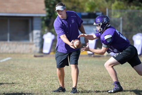 Mitchell head coach Travise Pitman hands off the ball to a player as she runs practice at the school in Bakersville on Oct. 9, 2019.