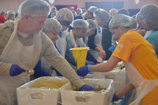 A table of volunteers sorts through crates of pasta at the third annual United Against Hunger event.