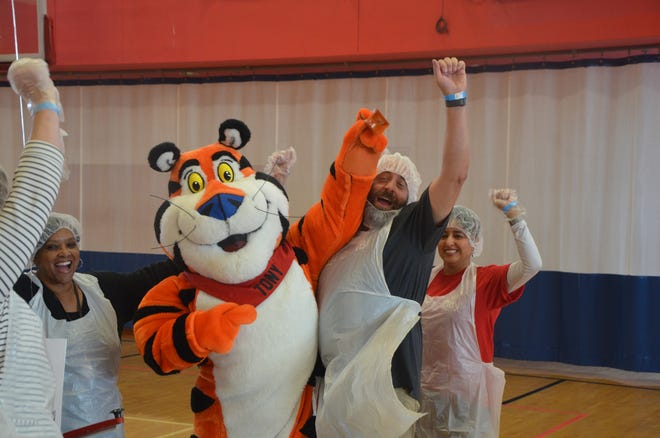 Volunteer Wilson Ray celebrates with Tony and Tiger after his table finished a box of meals at the third annual United Against Hunger event.