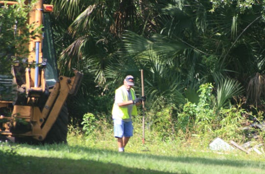 A worker with Palm Bay's Public Works Department takes part in Tuesday's dig for Brandy Hall's remains.