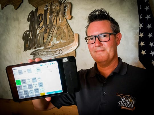Adam Mullin, tap room manager at Hell 'n Blazes Brewing Company in downtown Melbourne shows an iPad with a credit card attachment used by servers to take customer payment at the table.