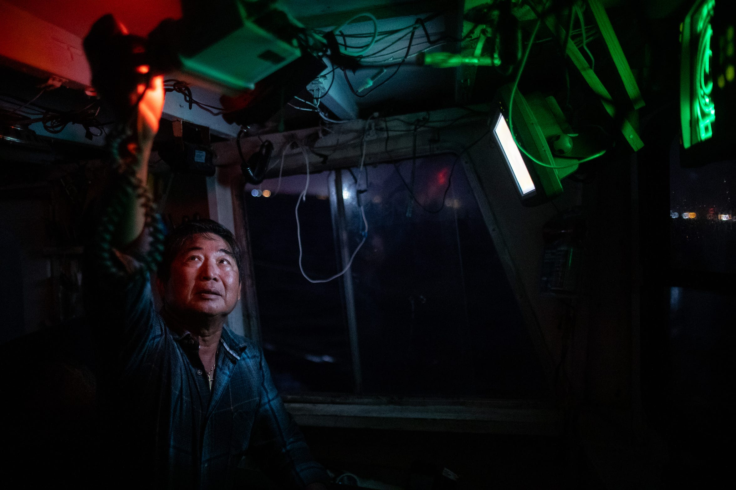 Doan Pham turns on a CB radio on his shrimping boat, Margie as he heads out in to Aransas Bay to shrimp before sunrise on Tuesday, Oct. 1, 2109.
