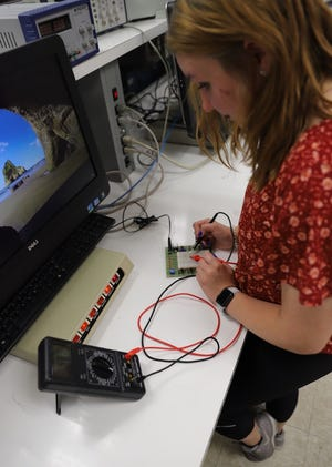 Miami University Regionals work+ program student Brittany Ashcraft checks a circuit with a multimeter. Ashcraft said she enrolled in the program to avoid post-graduation student loan debt.