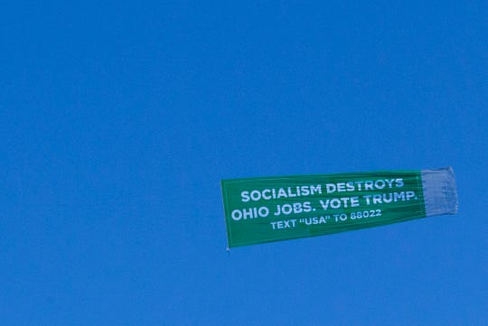 """A plane flies over Westerville, Ohio, with a banner that reads, """"SOCIALISM DESTROYS OHIO JOBS. VOTE TRUMP"""" on Oct. 15. The Trump campaign paid for the aerial banner to fly above Westerville for six hours before the Democratic presidential debate at Otterbein University."""