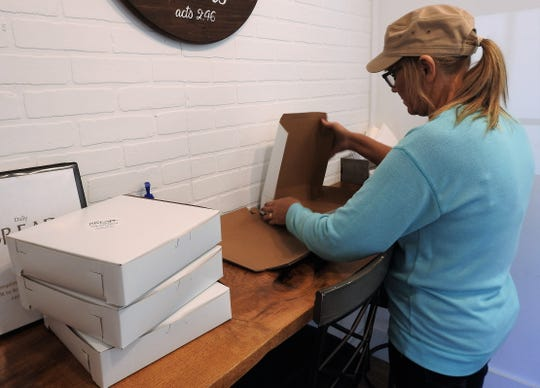 Tonia Wesney folds pastry boxes for use at Daily Bread Bakery and Cafe. The business opened Sept. 16 on South Seventh Street.