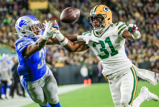 Green Bay Packers safety Adrian Amos breaks up a pass intended for Detroit Lions running back Kerryon Johnson at Lambeau Field in Green Bay, Wis., Oct. 14, 2019.