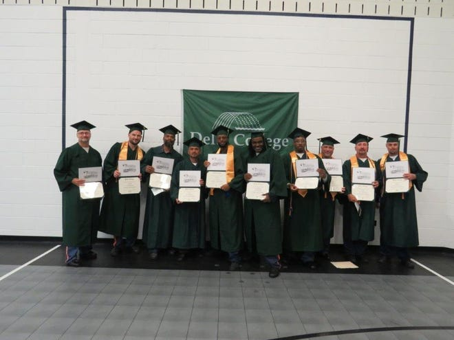 Inmates at Saginaw Correctional Facility are pictured after receiving their associate's degrees in business studies from Delta College.