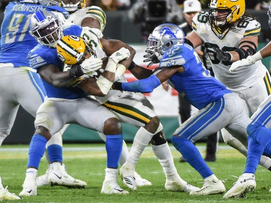Packers running back Aaron Jones is tackled by Lions linebacker Jarrad Davis, left, and safety Tavon Wilson, right, in the fourth quarter Oct. 14.