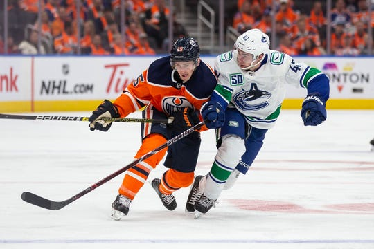 Vancouver Canucks' Quinn Hughes battles Josh Archibald of the Edmonton Oilers during the second period at Rogers Place on Oct. 2, 2019, in Edmonton, Canada.