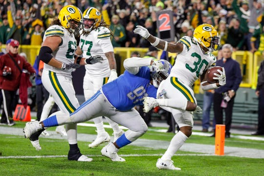 Packers' Jamaal Williams runs for a TD while breaking a tackle by Lions' A'Shawn Robinson during the first half Oct. 14, 2019, in Green Bay, Wis.