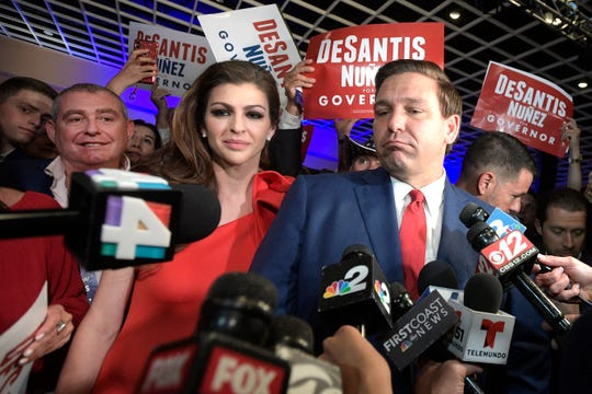 In this Nov. 6, 2018 file photo, Florida Govenor-elect Ron DeSantis, right, answers questions from reporters, with his wife Casey, after being declared the winner of the Florida gubernatorial race at an election party, in Orlando, Fla. Standing behind Casey DeSantis is Lev Parnas.