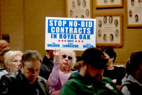A member of the public holds a sign denouncing no-bid contracts, one of several displayed during a Royal Oak City Commission meeting last week.
