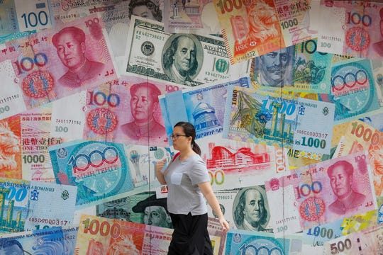 A woman walks by a money exchange shop decorated with different countries currency banknotes at Central, a business district in Hong Kong.