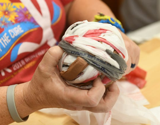 "Jeannine Ayers of Wyandotte rolls ""plarn"" into a ball. The Bag Ladies with a Cause meet Tuesday evenings to make ""plarn"" from plastic bags and crochet them into mats for the homeless."