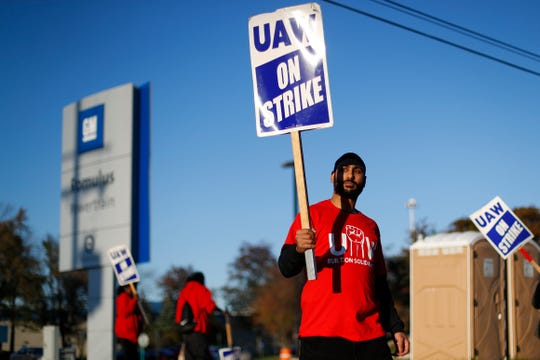 A member of the United Auto Workers walks the picket line at the General Motors Romulus Powertrain plant in Romulus on Oct. 9.