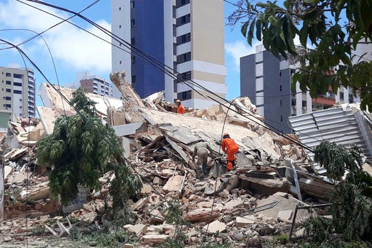 Firefighters search for people who are trapped after a building collapsed in Fortaleza, Ceara state, Brazil, Tuesday, Oct. 15, 2019.