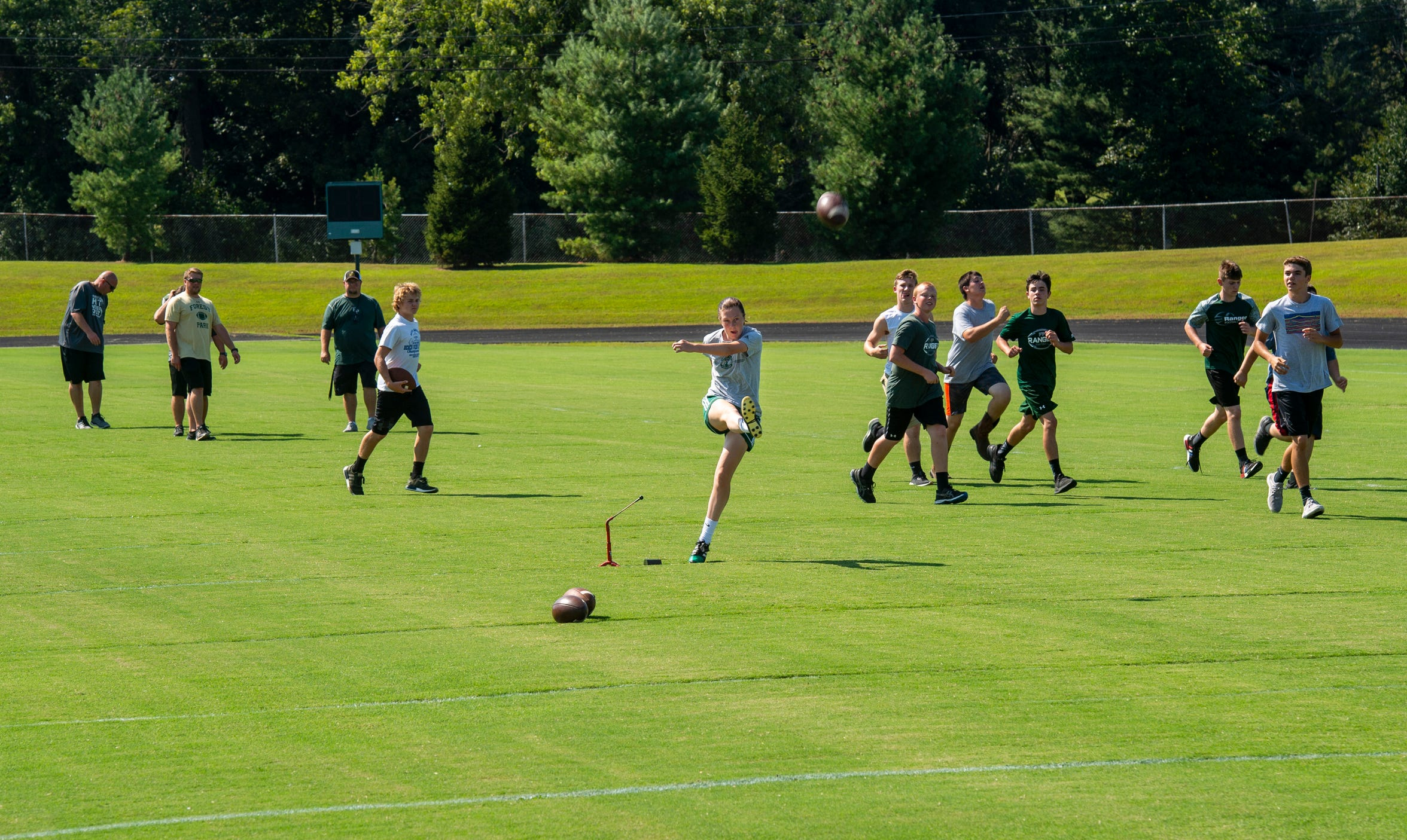 Abby Eckert kicks field goals as her Forest Park football teammates warm up at practice. After 30 minutes of football, Eckert heads to soccer practice.