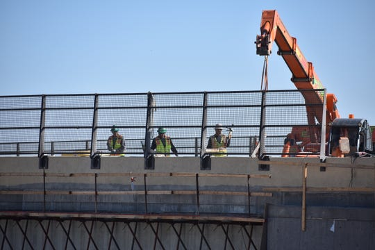 Workers on Tuesday, Oct. 15, 2019, put finishing touches on the new Colorado Highway 402 bridge over Interstate 25. The road is schedule to reopen Friday after being closed for four months.