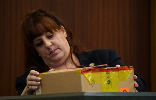 Linda Otterstatter, a forensics examiner with the FBI, inspects an evidence box while on the witness stand Tuesday morning. The Jimmy Rodgers trial continued on Tuesday, October 15, 2019, for day 4 of testimony at the Lee County Justice Center in Fort Myers. Rodgers is on Trial for the murder of Teresa Sievers.