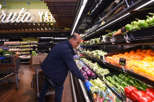 Pay-Less produce supervisor Marlon Macdon stocks the produce section at the new store in Maite, Oct. 15, 2019.