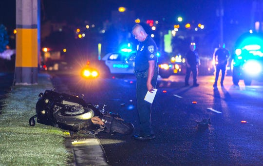 A Guam Police Department Highway Patrol Division officer looks down on a wrecked motorcycle laying in the gutter as he and other GPD officers conduct an investigation of the fatal crash that ended the life of Leroy Leon Guerrero Jr. on Route 8, near the Government of Guam Retirement Fund in Maite, on Oct. 14, 2019.