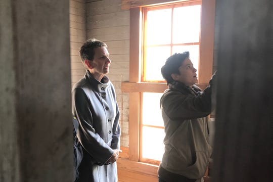 Johnson County Supervisor Pat Heiden and Vanessa Fixmer-Oraiz of Astig Planning LLC peer to look at the etchings on the walls of the asylum at the Johnson County Historic Poor Farm on Tuesday, October 15, 2019.