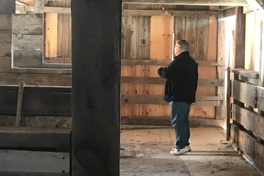 Supervisor Rod Sullivan looks around the original horse stalls inside the West Barn at the Johnson County Historic Poor Farm on Tuesday, October 15.