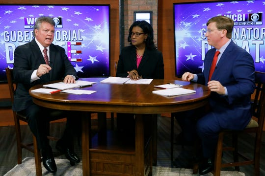Democratic Attorney General Jim Hood, left, responds to a question while Republican Lt. Gov. Tate Reeves, left, and moderator and WCBI anchor Aundrea Self listen during the second televised gubernatorial debate in Columbus, Miss., Monday, Oct. 14, 2019.