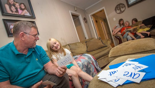 Billy Green, of Brandon, Mississippi, left, sits in his living room with granddaughter Claire Green, 6, working on a reading lesson with word cards as his wife, Lynne, reads a story to Hannah, 8, right, with Kiersten, 10, looking on.