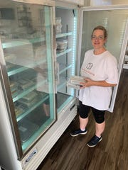 Teresa Sones checks the supply of homemade frozen entrees at Bless This Food Catering in Flora.