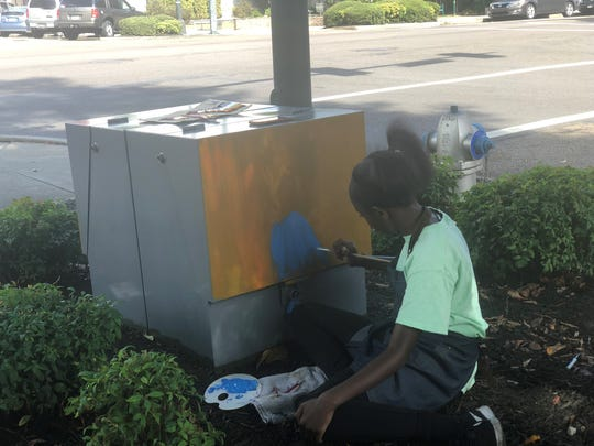 Nine-year old Ava Ingle paints on the electrical box at the corner of E. Main Street and Liberty St. as part of Mayor Scott Conger's Public Art Initiative.