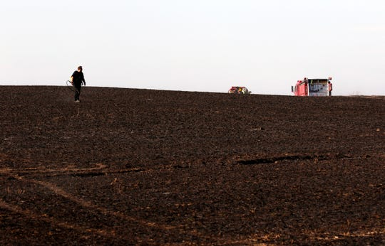 A firefighter carrying a backpack of water walks through a charred field Tuesday afternoon, Oct. 15, 2019, in the 6200 block of Crumley Road in Amanda Township. Firefighters from seven county fire departments responded to the field fire which burned seven to eight acres before it was brought under control. The fire was started by a resident burning brush near the field and the fire spreading to engulf the acreage.