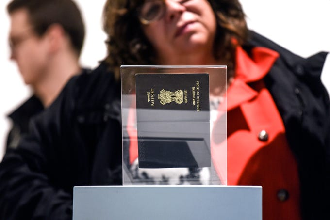 """Vivek Vellanki's grandmother's passport is displayed at the end of the """"Do you have anything to declare?"""" exhibit on Monday, Oct. 14, 2019, at the MSU Union Art Gallery in East Lansing. The exhibit explores the relationship between the identities of immigrants and refugees and their passport photos."""