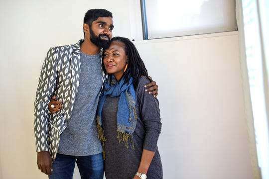 """Michigan State University doctoral student Vivek Vellanki, left, hugs friend Molade Osibodu during the opening reception of his exhibition """"Do you have anything to declare?"""" on Monday, Oct. 14, 2019, at the MSU Union Art Gallery in East Lansing. The exhibit explores the relationship between the identities of immigrants and refugees and their passport photos."""