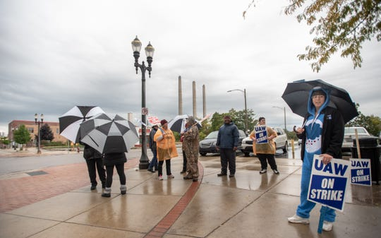 "UAW Local 652 members, including Elizabeth Jones, right, brave the elements while picketing near the east entrance of the General Motors Lansing Grand River Assembly Plant Friday, Oct. 11, 2019.  Jones has worked at GM for seven years.  She's dressed as Grumpy Bear from the series ""Care Bears."""