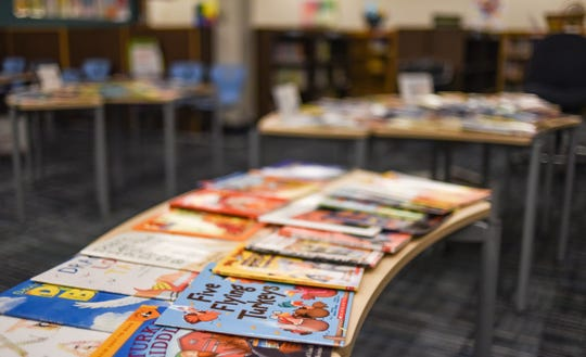 Tables of books in the library at Riddle Elementary School in Lansing. Students were able to choose one book each as part of the Lansing Reading is Fundamental program.