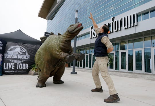John Palmeri, a paleoveterinarian with Jurassic World, gets Olive, a 6 foot tall, 3 foot wide baby stegosaurus, to stand up on two legs in front of Fiserv Forum in Milwaukee on Oct. 15.