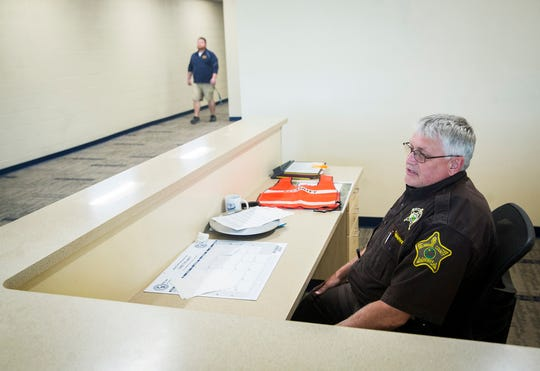 Officer Gary Marvin sits at a newly constructed security desk at Delta High School.
