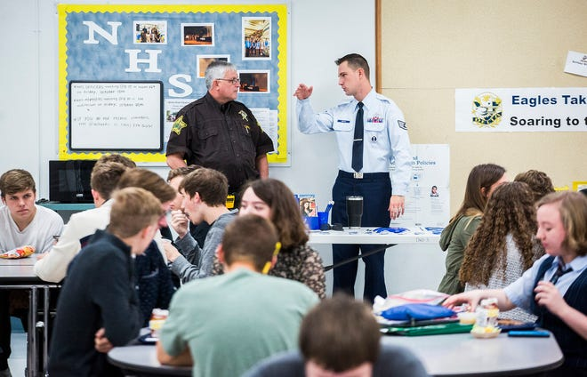 Officer Gary Marvin chats with an Airforce recruiter in the lunchroom of Delta High School.