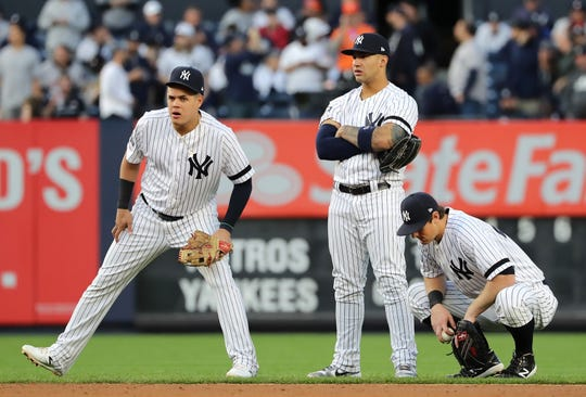 (L-R) Gio Urshela #29, Gleyber Torres #25 and DJ LeMahieu #26 of the New York Yankees wait as the home plate umpire is replaced following the fourth inning in game three of the American League Championship Series between the Houston Astros and the New York Yankees at Yankee Stadium on October 15, 2019 in New York City.